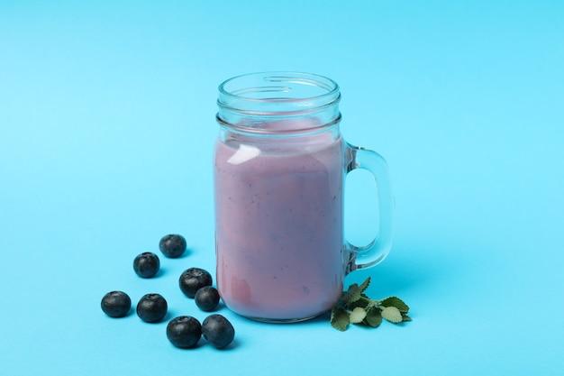 Свежий черничный смузи и ингредиенты на синем фоне
