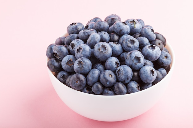 Fresh blueberry in white bowl on  pink background. side view.