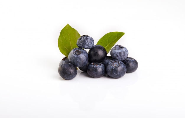 Fresh blueberry with green leaves isolated on white