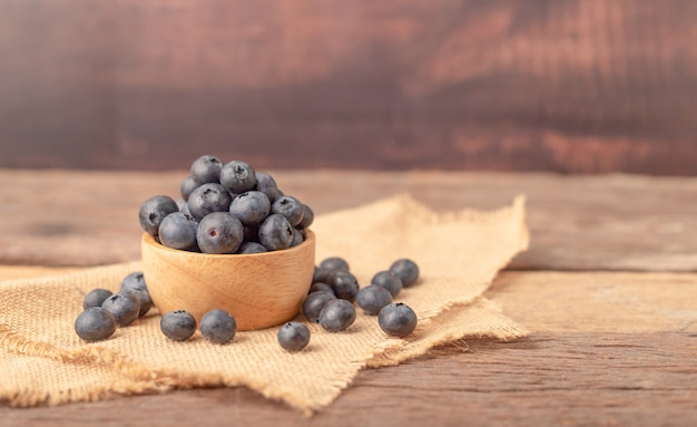 Fresh blueberry in a wood bowl and heap on the sack