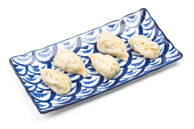 プレート上の新鮮な沸騰した餃子。背景に熱い蒸気を入れた中華料理。