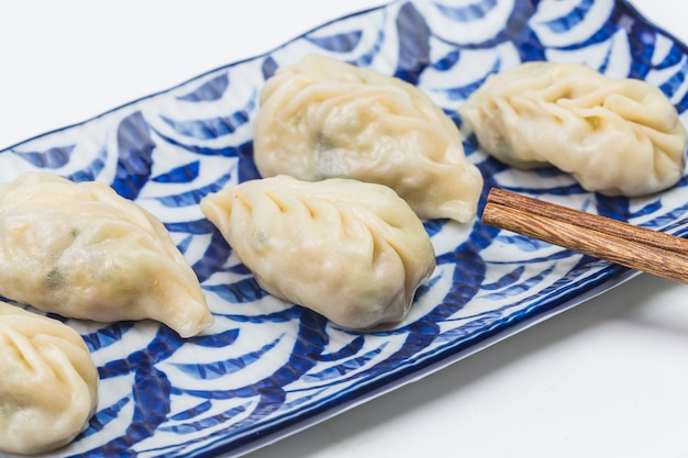 Fresh boiled dumpling on plate. chinese food with hot steams on background.