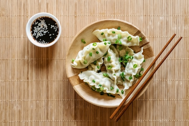 Fresh boiled gyoza dumplings with hot steams on wooden plate