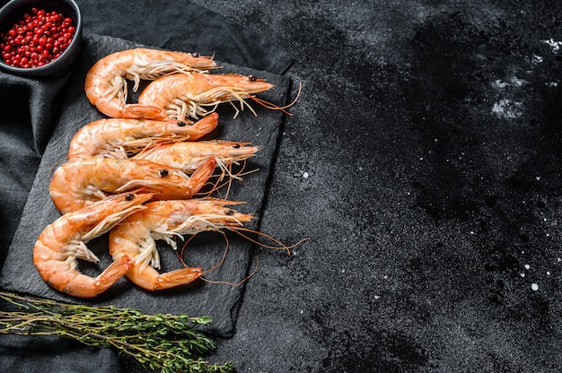 Fresh boiled prawns, shrimps on a stone board. black background