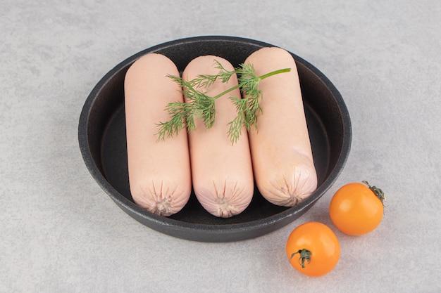 Свежие вареные сосиски и помидоры черри на черной тарелке.