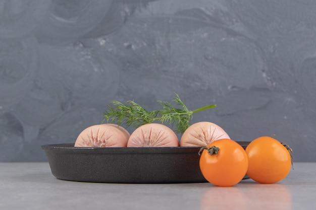 검정 잉크 판에 신선한 삶은 소시지와 체리 토마토.