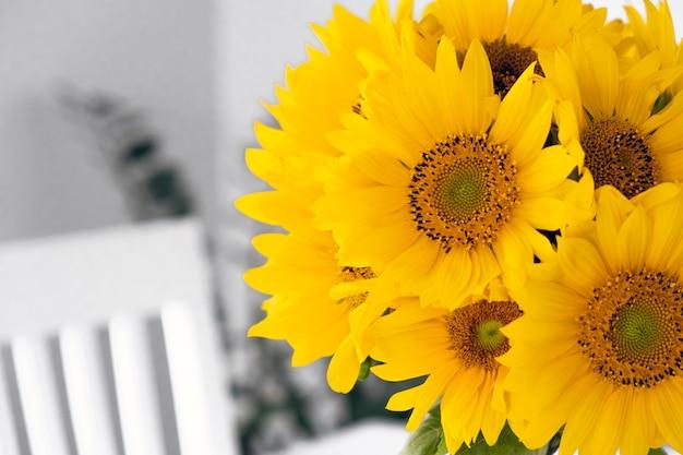 Свежий букет подсолнухов ромашек в стеклянной вазе в домашнем интерьере уютная атмосфера или летнее настроение