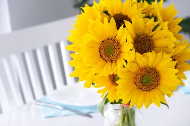 夕食に出されるテーブルの上の花瓶のひまわりの新鮮な花束家のインテリアで居心地の良い雰囲気