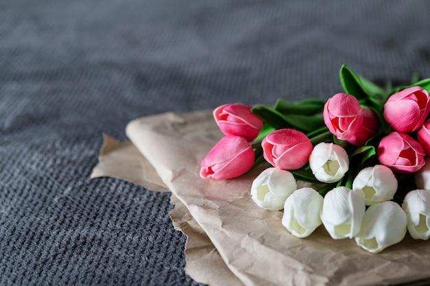 灰色の背景に再生紙の上に白とピンクのチューリップの新鮮な花束