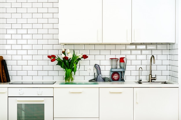Fresh bouquet of red and white tulips on kitchen table. detail of home interior, design.