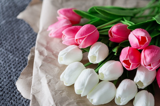 Fresh bouquet of white and pink tulips over recycled paper on gray background