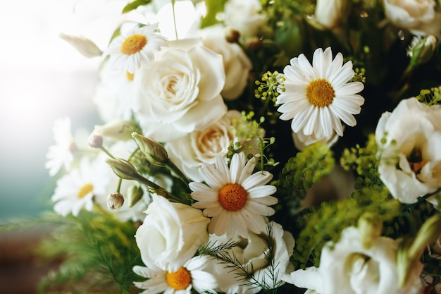 Fresh bouquet of white rose and chamomile close up