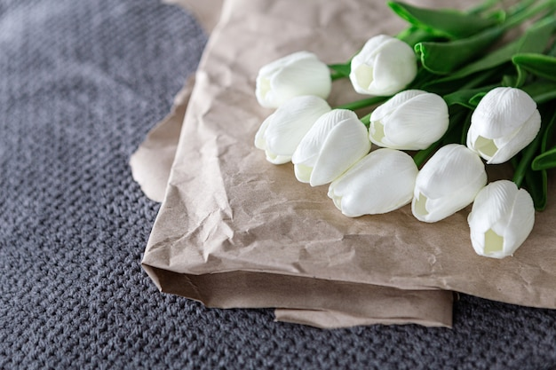 Fresh bouquet of white tulips over recycled paper on gray background