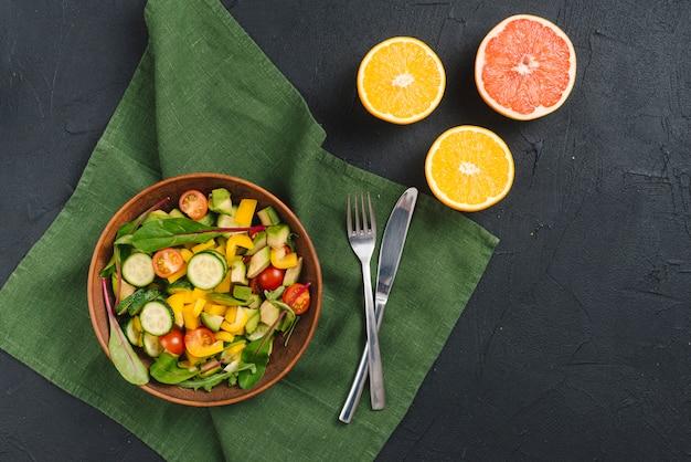 Fresh bowl of vegetable salad; oranges and grapefruits on black concrete background