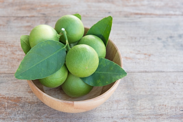 Fresh branch of limes in wood bowl on old wooden table