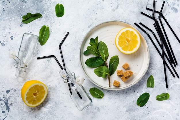古いコンクリートの背景のセラミックプレート上のミント、レモン、サトウキビの新鮮な枝。