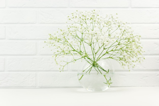 カスミソウの白い花の新鮮な枝がガラスの花瓶に立っています。
