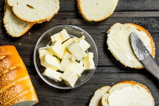 焼きたてのパンとバター。木製の背景に。