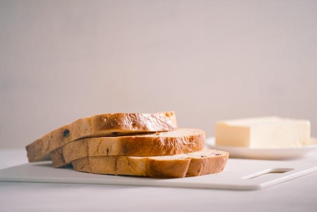 Свежий хлеб и домашнее масло на белом столе