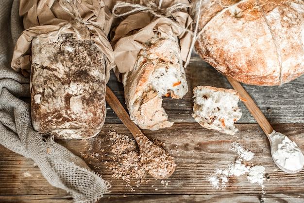 Свежий хлеб и деревянная ложка на старых деревянных фоне