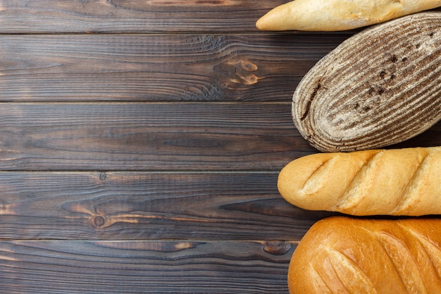 Fresh bread assortment on wooden surface background