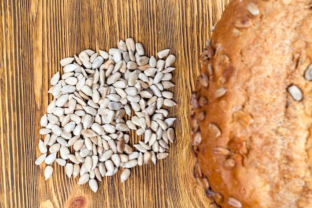 テーブルの上に一緒に横たわっている焼きたてのパン焼きと生のヒマワリの種