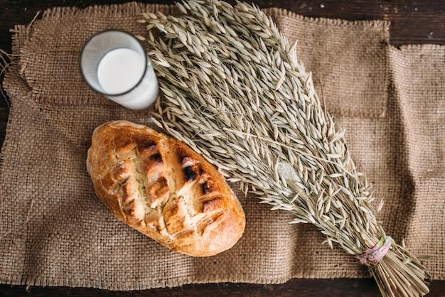 サクサクした皮、小麦の束、黄麻布、上面にガラスの牛乳と焼きたてのパンのパン