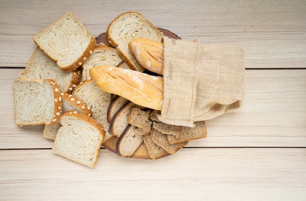 Fresh bread in burlap sack on wooden table. top view with space for your text.