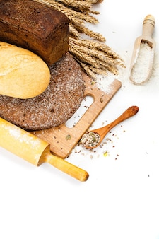 Fresh bread on cutting board, scoop with flower and seeds isolated over white