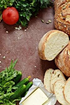 На обед свежий хлеб из цельной пшеницы со сливочным маслом, фреш, зелень и овощи.