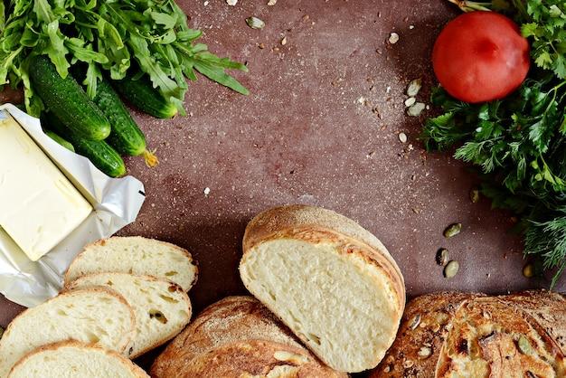 全粒小麦とバター、新鮮なハーブ、野菜を使ったランチ用の焼きたてのパン。