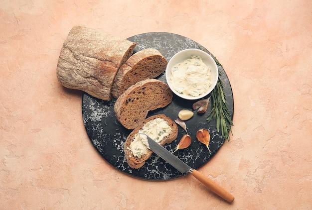 신선한 빵, 마늘 버터 및 재료 색상 배경 프리미엄 사진