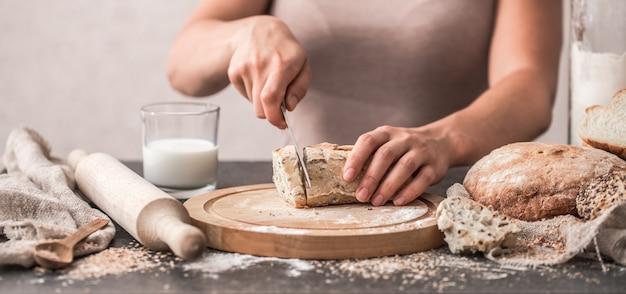 古い木製の背景に手のクローズアップで焼きたてのパン
