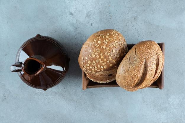 Свежий хлеб в деревянной коробке с классической бутылкой.
