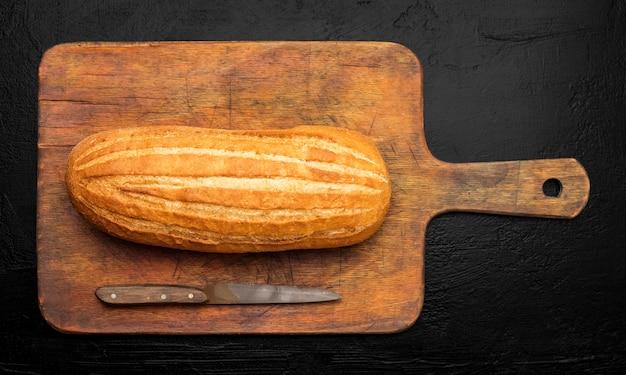 Свежий хлеб на старой разделочной доске. черный фон. вид сверху с местом для вашего текста