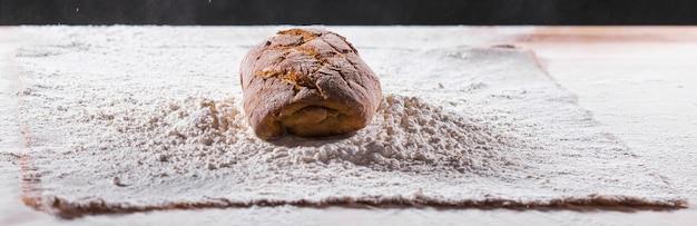 小麦粉プレーサーのテーブルのクローズアップの焼きたてのパン。台所のテーブルの焼きたてのパン。健康的な食事と伝統的なパン屋のコンセプト。素朴なスタイル。