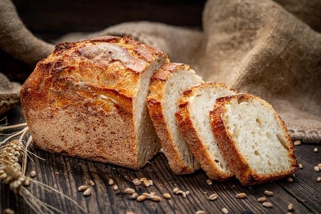 Свежий хлеб на деревянной земле. свежеиспеченный традиционный хлеб на деревянном столе. здоровая пища