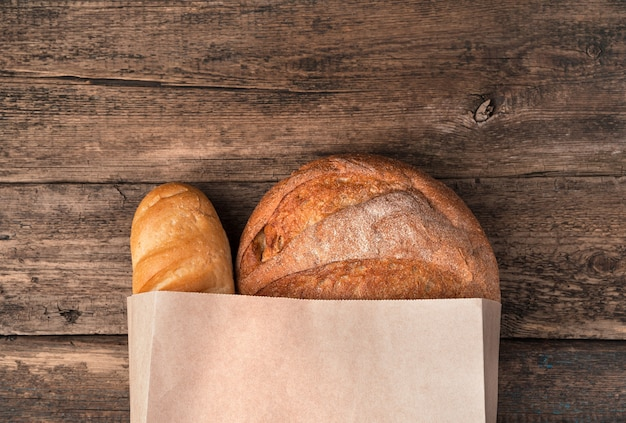 Fresh bread in a paper bag on a wooden surface