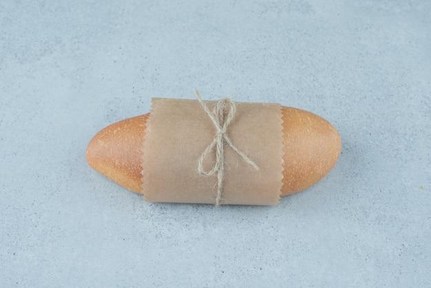 石の表面にロープで結ばれた焼きたてのロールパン