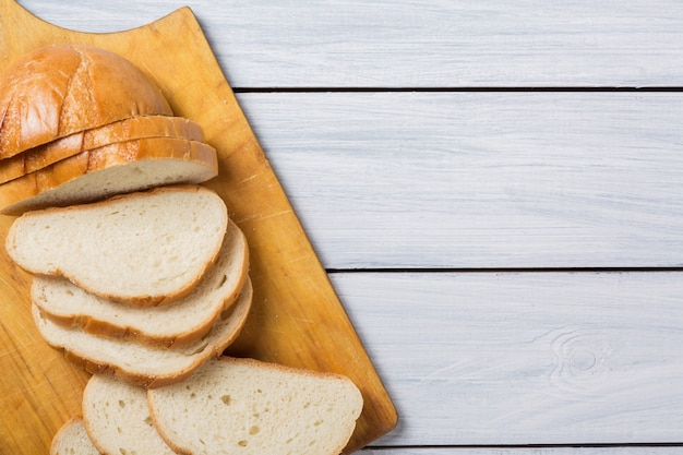 Fresh bread slices on cutting board against white wooden background.