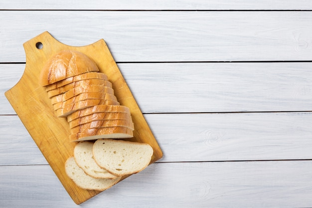 Fresh bread slices on cutting board against white wooden background