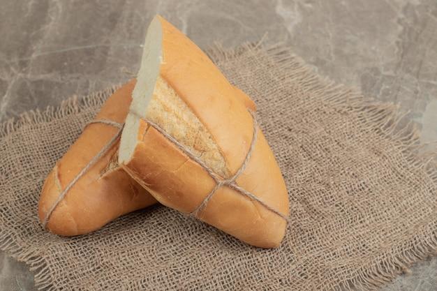 Pane fresco legato con corda su marmo. foto di alta qualità