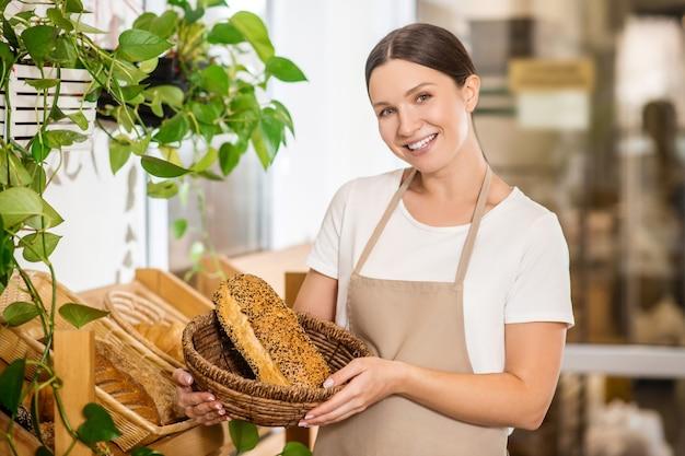 Свежий хлеб. приветствуя молодую взрослую женщину в фартуке с корзиной свежеиспеченного аппетитного хлеба в магазине пекарни