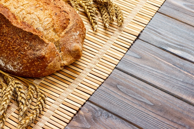Fresh bread and wheat on the wooden table