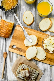 Fresh bread with butter and orange juice . on wooden rustic surface