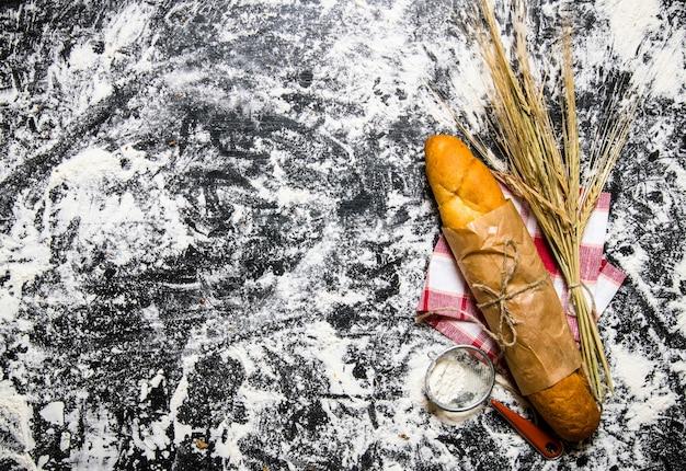 小麦と小麦粉の耳を持つ焼きたてのパン。小麦粉と一緒にテーブルの上。テキスト用の空き容量。上面図