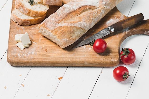 Fresh bread with knife on cutting board