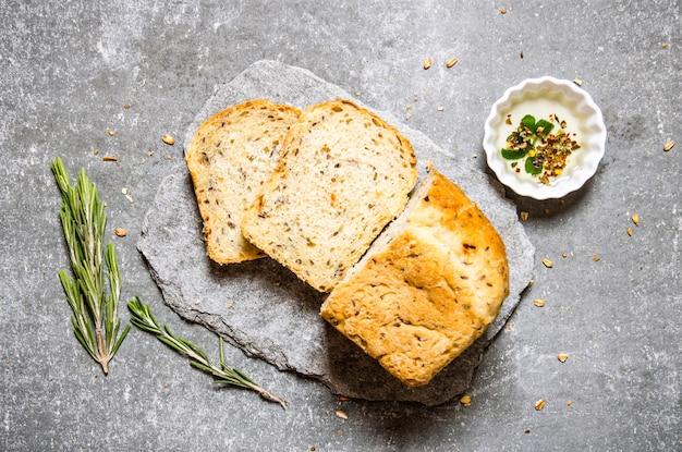 기름과 로즈마리를 곁들인 신선한 빵. 돌 테이블에. 평면도