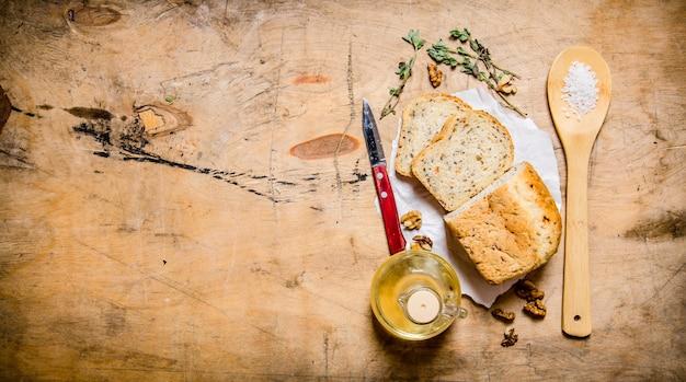 기름, 소금 및 허브와 함께 신선한 빵. 나무 테이블에. 텍스트를위한 여유 공간. 평면도