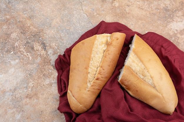 大理石の背景に赤いテーブルクロスと焼きたてのパン